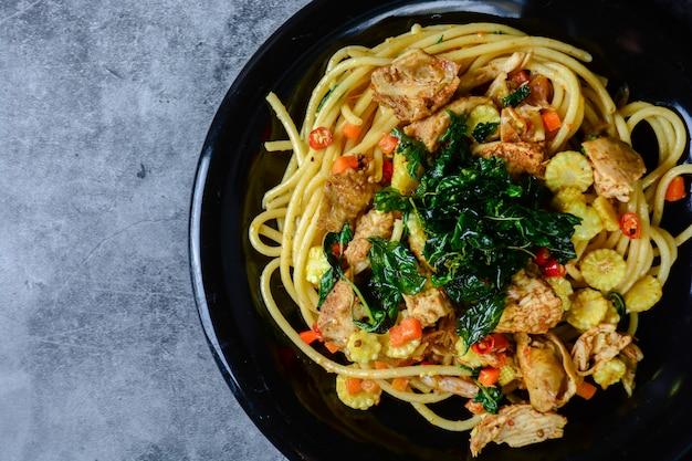 Spaghetti di pollo caldi e piccanti, conditi con basilico croccante e mais a fette