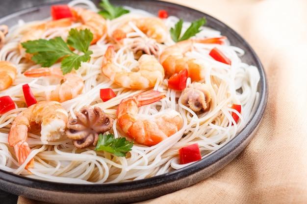 Spaghetti di riso con gamberetti o gamberi e piccoli polpi sul piatto di ceramica grigia su uno sfondo di cemento nero