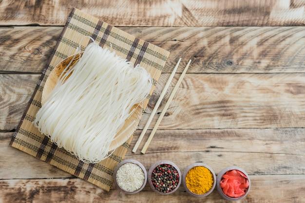 Spaghetti di riso crudo con le bacchette e ciotole di spezie secche sul tavolo