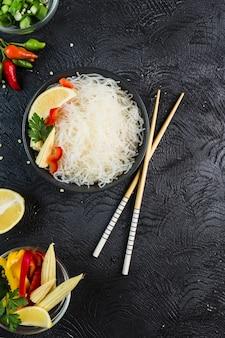 Spaghetti di riso funchosa con le verdure in una ciotola nera con le bacchette su uno sfondo scuro, vista dall'alto, flatlay.