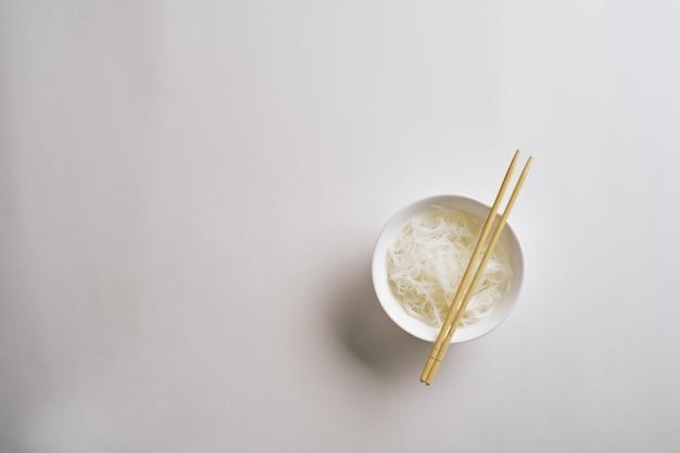 Spaghetti di riso in un piatto. tagliatelle di riso bollite in un piatto su uno sfondo bianco