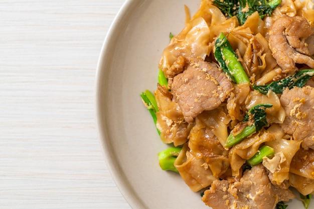 Spaghetti di riso saltati in padella con salsa di soia nera e maiale e cavolo nero, stile asiatico