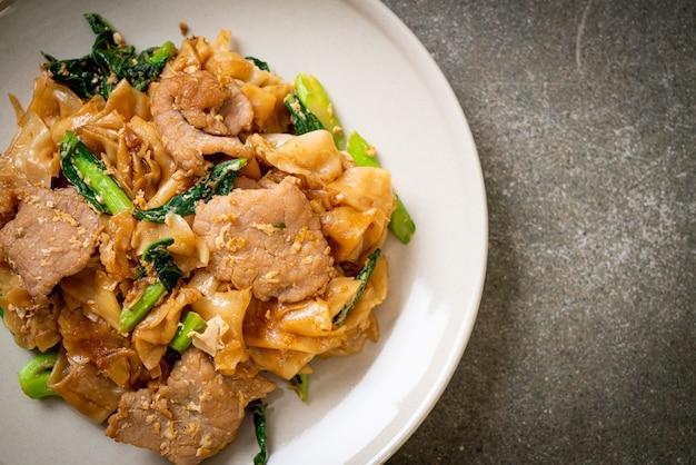 Spaghetti di riso saltati in padella con salsa di soia nera e maiale e cavolo nero
