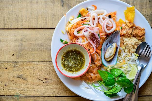 Spaghetti di riso saltati in padella (pad thai) con gamberi, cozze e calamari.