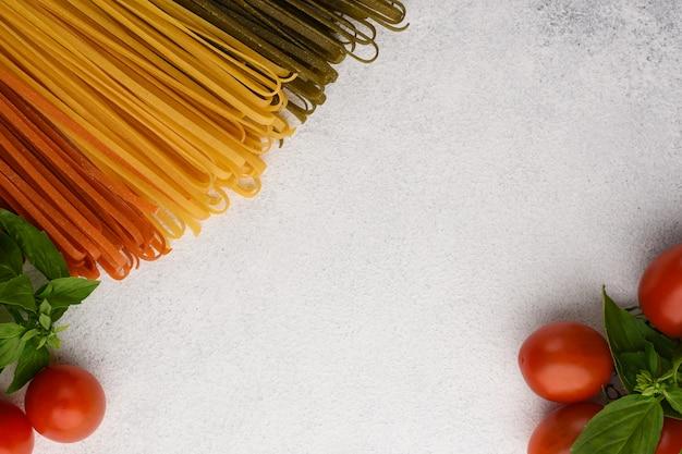 Spaghetti di verdure con pomodorini e cornice di basilico. ingredienti della pasta su fondo di pietra bianco con lo spazio della copia.