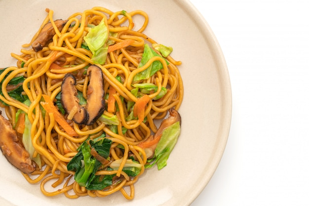 Spaghetti di yakisoba saltati in padella con verdure isolate su sfondo bianco - cibo vegano e vegetariano