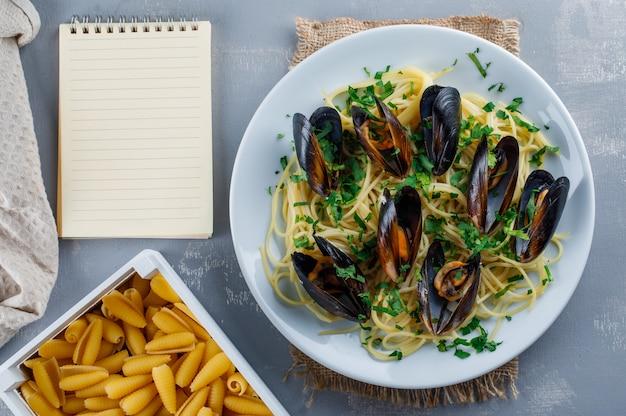 Spaghetti e cozze in un piatto con quaderno, pasta cruda, asciugamano da cucina