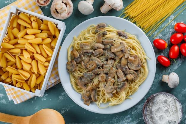 Spaghetti e funghi con pasta cruda, pomodoro, farina, cucchiaio di legno in un piatto su intonaco