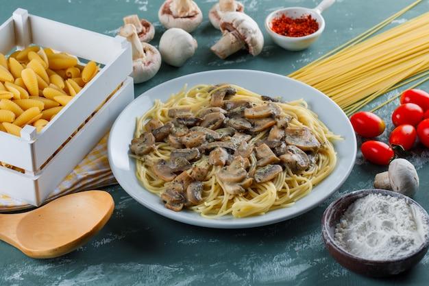 Spaghetti e funghi con pasta cruda, pomodoro, farina, spezie, cucchiaio di legno in un piatto