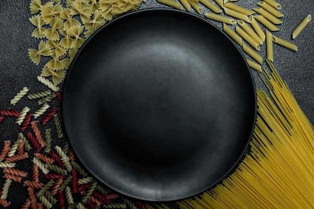 Spaghetti e pasta lunghi gialli su fondo grigio