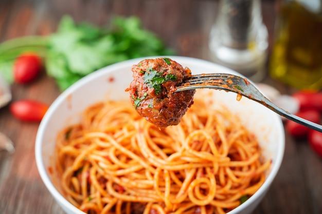 Spaghetti e polpette con salsa di pomodoro in ciotola bianca sul bordo rustico in legno