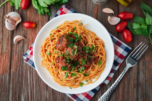 Spaghetti e polpette con salsa di pomodoro in piatto bianco sul bordo rustico in legno