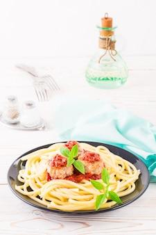 Spaghetti e polpette in salsa al pomodoro con foglie di basilico fresco su un piatto