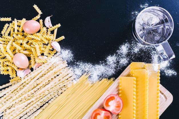 Spaghetti grezzi su fondo di legno nero, vista superiore