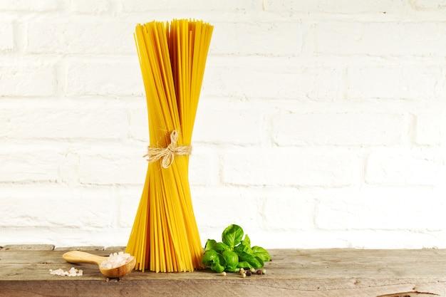 Spaghetti gustosi freschi freschi italiani sul tavolo della cucina sullo sfondo della cucina. cottura o concetto di alimenti sani.