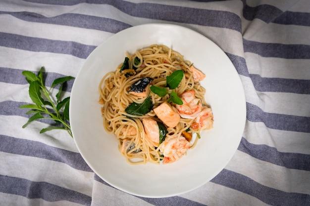 Spaghetti in padella con salmone, gamberetti e stomaco in una ciotola bianca su un tavolo di legno