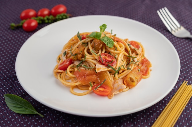 Spaghetti in padella splendidamente disposti in un piatto bianco.