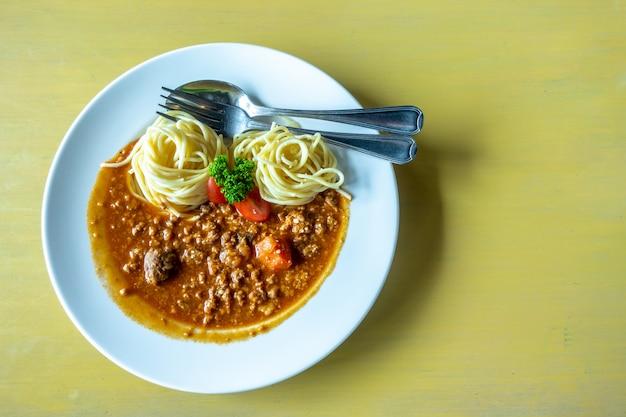 Spaghetti in salsa di pomodoro con carne di maiale e forchetta