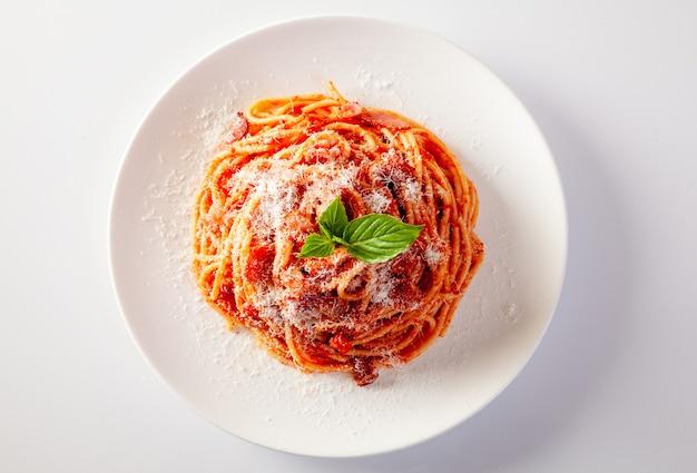 Spaghetti in un piatto su uno sfondo bianco