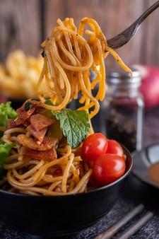 Spaghetti in una tazza nera con pomodori e lattuga.