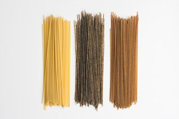 Spaghetti interi della pasta tricolora su una priorità bassa bianca