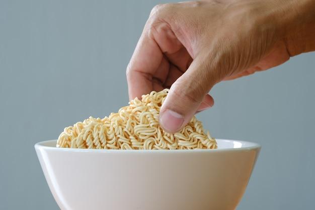 Spaghetti istantanei crudi e ciotola bianca sulla tavola di legno