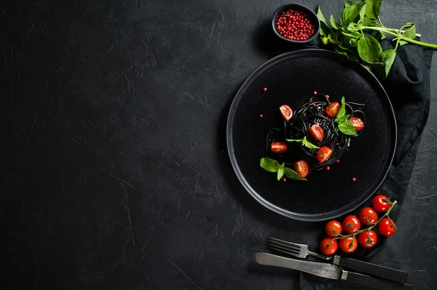 Spaghetti neri con basilico e pomodorini, pasta vegetariana.