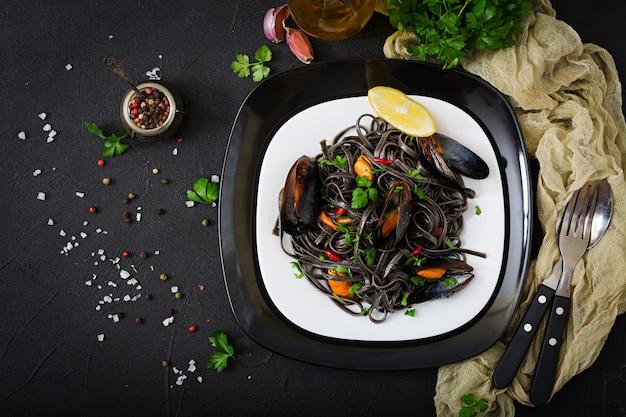 Spaghetti neri. pasta nera dei frutti di mare con le cozze sopra la tavola nera. cibo prelibatezza mediterranea. disteso. vista dall'alto