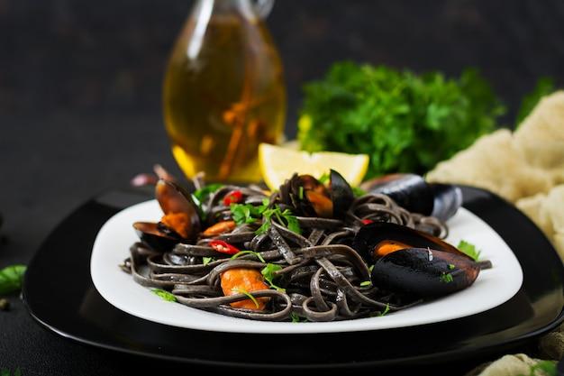 Spaghetti neri. pasta nera dei frutti di mare con le cozze sopra la tavola nera. cibo prelibatezza mediterranea
