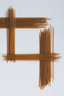 Spaghetti simmetrici della pasta su una priorità bassa bianca
