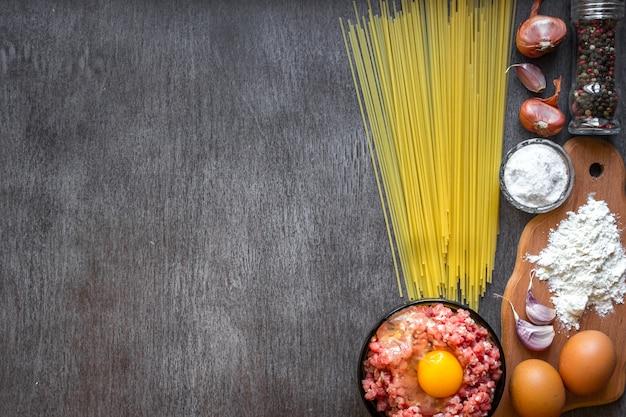 Spaghetti, uova, olio d'oliva, aglio, carne macinata, pepe e sedano fresco su fondo di legno