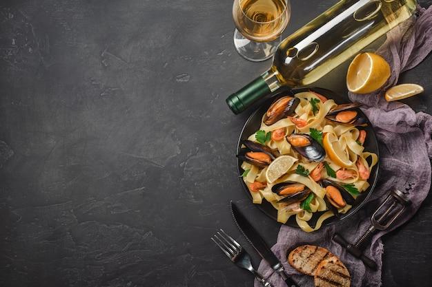 Spaghetti vongole, pasta italiana di mare con vongole e cozze, in piatto con erbe e bicchiere di vino bianco su fondo rustico in pietra.