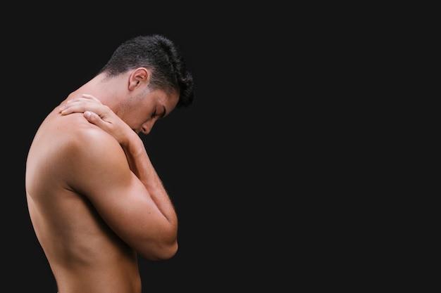 Spalla di sfregamento ragazzo muscoloso
