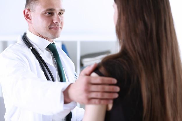 Spalla paziente amichevole della stretta maschio del medico in ufficio