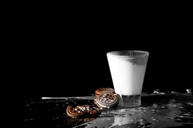 Spalsh in bicchiere di latte e biscotti al cioccolato nero