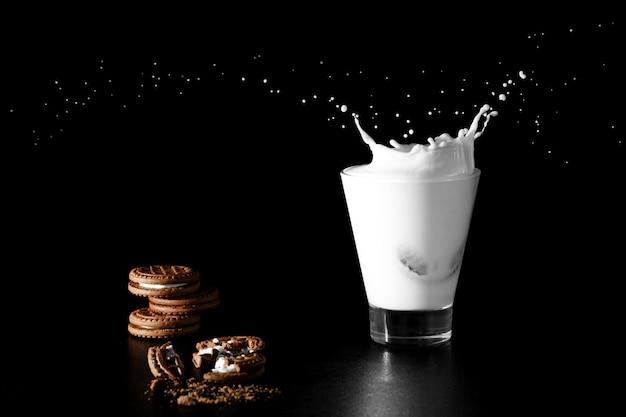 Spalsh in bicchiere di latte e biscotti al cioccolato sul nero