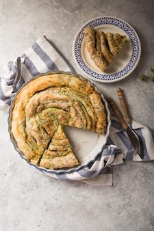 Spanakopita greco della torta sopra fondo concreto. idee e ricette per la torta di spinaci vegetariana o vegana da pasta fillo tagliata a fette