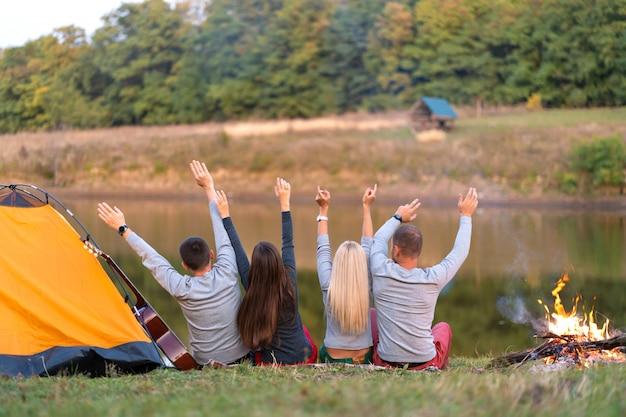 Sparare da dietro, un gruppo di amici felici che si accampano sulla riva del fiume, ballano, tengono le mani in alto e godono della vista, vacanze divertenti
