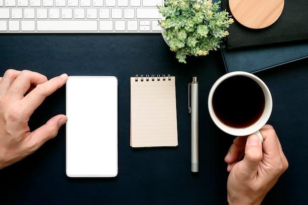 Sparato della mano dell'uomo che tocca allo schermo dello smartphone e che tiene tazza di caffè mentre lavorando all'ufficio.