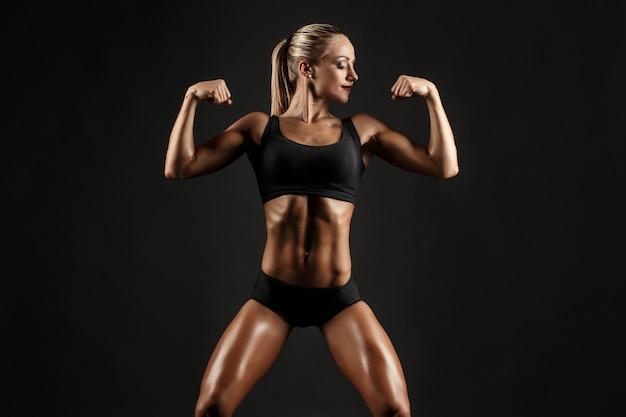 Sparato della ragazza bionda femminile sportiva che mostra indietro il suo corpo perfetto sul nero