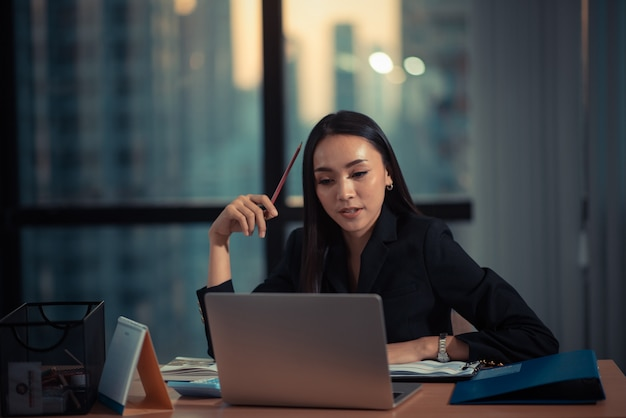 Sparato di bella giovane donna di affari che per mezzo del computer portatile e facendo un certo lavoro di ufficio mentre lavorando al computer portatile