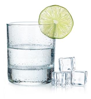 Sparato di tequila con una fetta di calce su fondo bianco