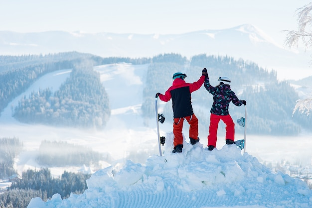 Sparato di una coppia che si fiving l'un l'altro in posa sopra una montagna nevosa