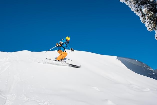 Sparato di uno sciatore freeride professionista che scia nelle montagne un giorno di inverno soleggiato