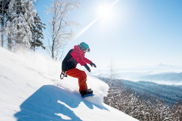 Sparato di uno snowboarder di freeride che guida nelle montagne che indossano il giorno soleggiato di inverno del bello paesaggio dell'attrezzatura di snowboard
