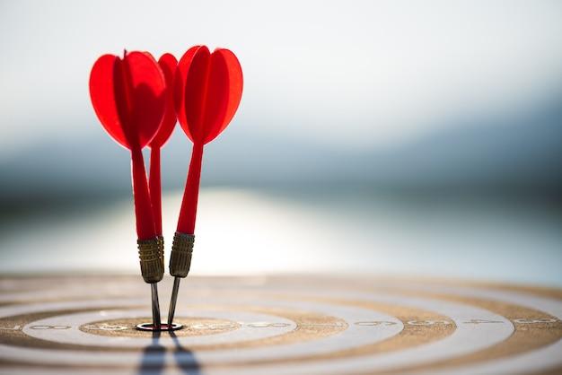 Sparato frecce rosse delle freccette nel centro dell'obiettivo, obiettivo di affari o concetto di successo di scopo