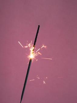 Sparkler che brucia sul colore rosa