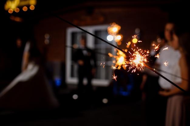 Sparkler in fiamme sul buio. spazio per il testo. felice anno nuovo e buon natale concetto. buone vacanze. messa a fuoco selettiva