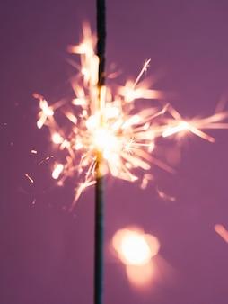 Sparkler stick che brucia sul rosa