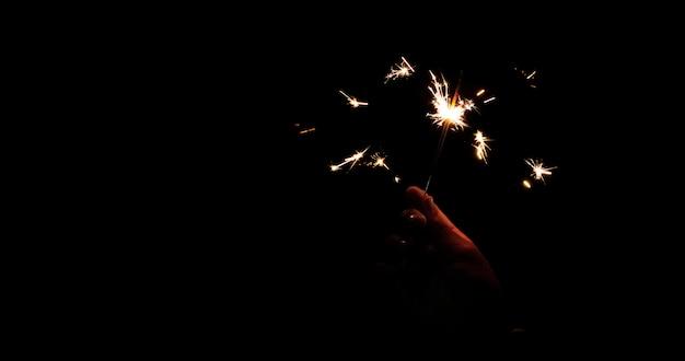 Sparklers astratti della sfuocatura per il fondo di celebrazione, movimento dal vento vago bruciatura della tenuta della mano
